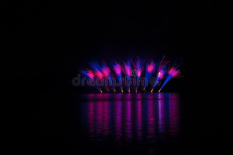 Bristningar av blå och violett brand i rika fyrverkerier över Brnos fördämning med sjöreflexion royaltyfri foto