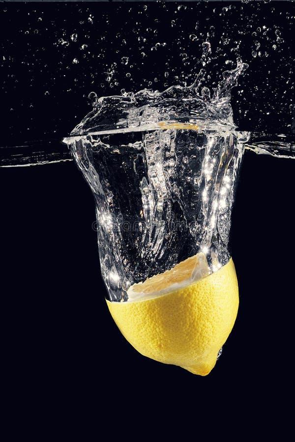 Bristningar och färgstänk från en citron som kastas in i vattnet royaltyfria foton