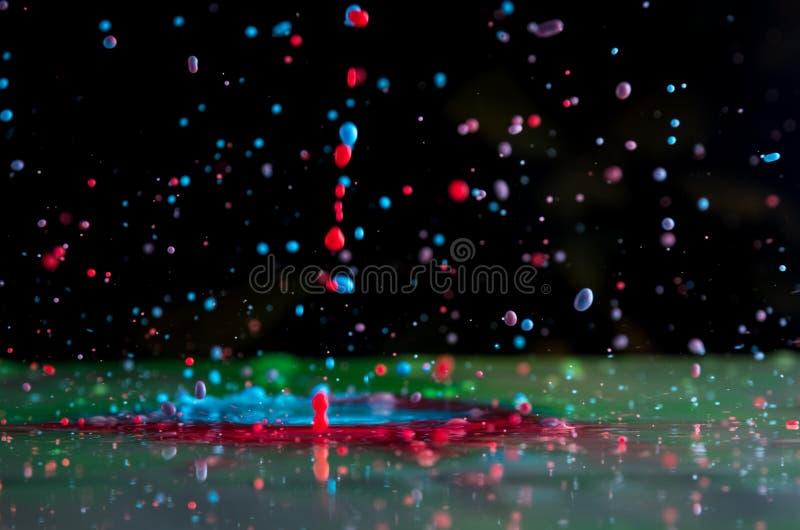 Bristningar och färgstänk från fallande målarfärger av olika färger fotografering för bildbyråer