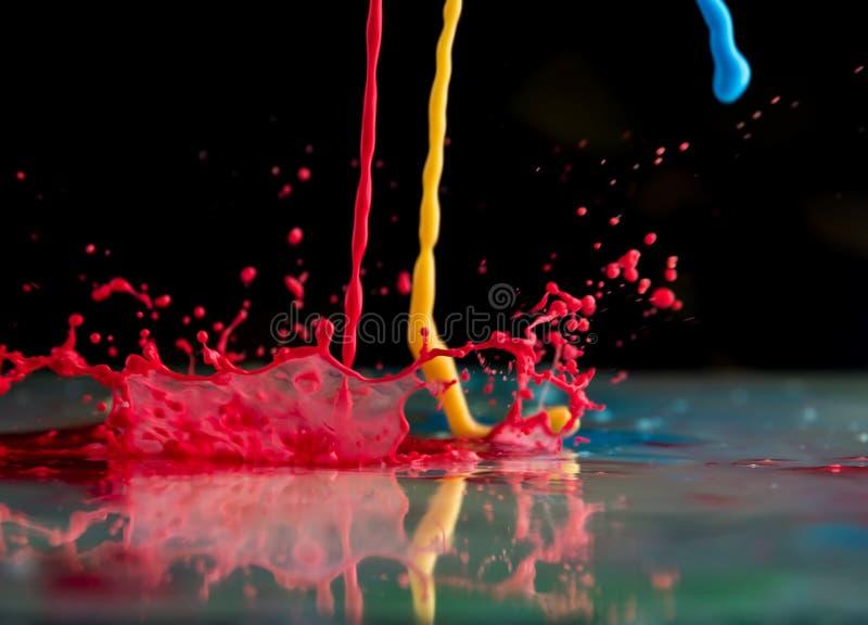 Bristningar och färgstänk från fallande målarfärger av olika färger royaltyfri foto