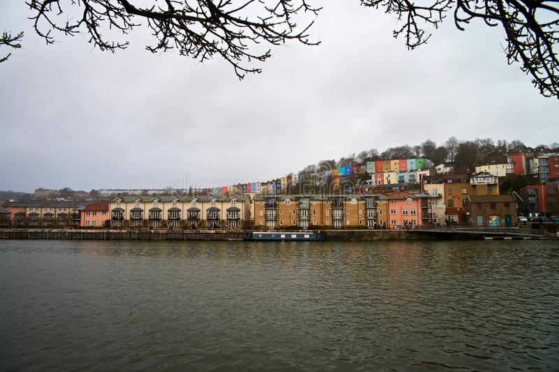 Bristol Cityscape, with colourful houses. Over the river. Framing with branches royalty free stock photography