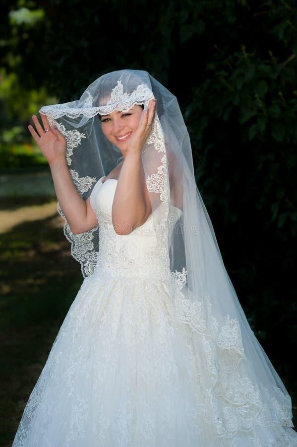 Brite die haar bruidssluier met twee handen open houden royalty-vrije stock foto's