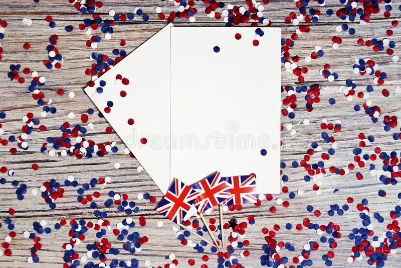 BRITISCHE Flagge auf hölzernem Hintergrund mit Konfettis und Weißbuchblättern, Plan, Kopienraum das Konzept des Unabhängigkeitsta stockfotografie