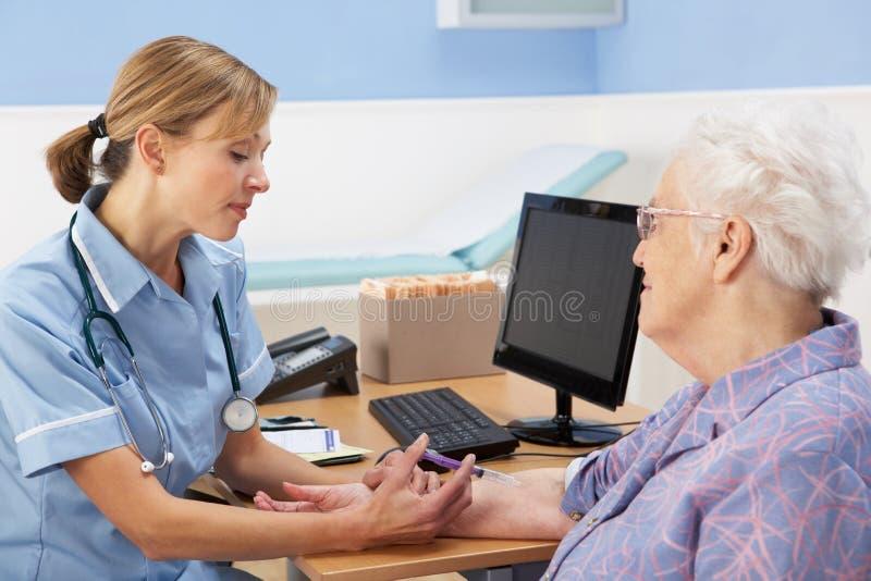 BRITISCHE Krankenschwester, die älteren Frauenpatienten einspritzt stockbild