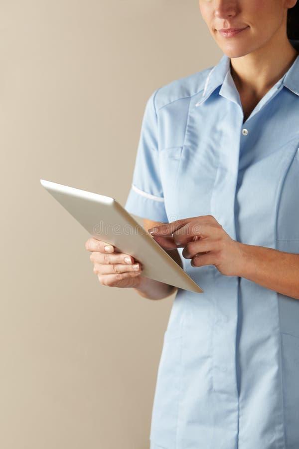 BRITISCHE Krankenschwester, die Computertablette verwendet stockbilder