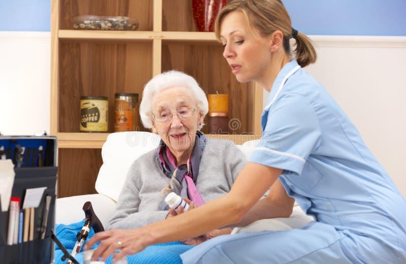 BRITISCHE Krankenschwester, die zu Hause ältere Frau besucht stockbild