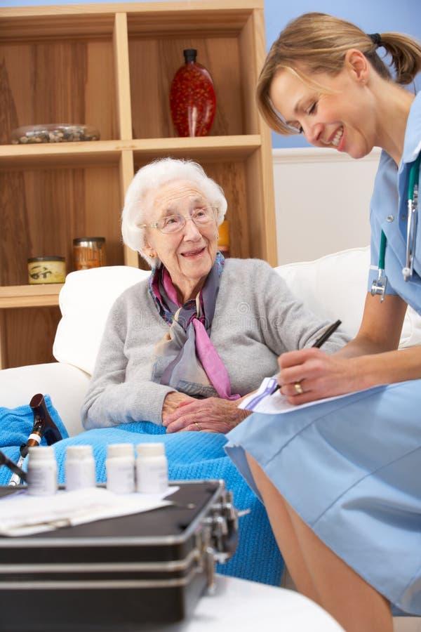 BRITISCHE Krankenschwester, die zu Hause ältere Frau besucht stockfoto
