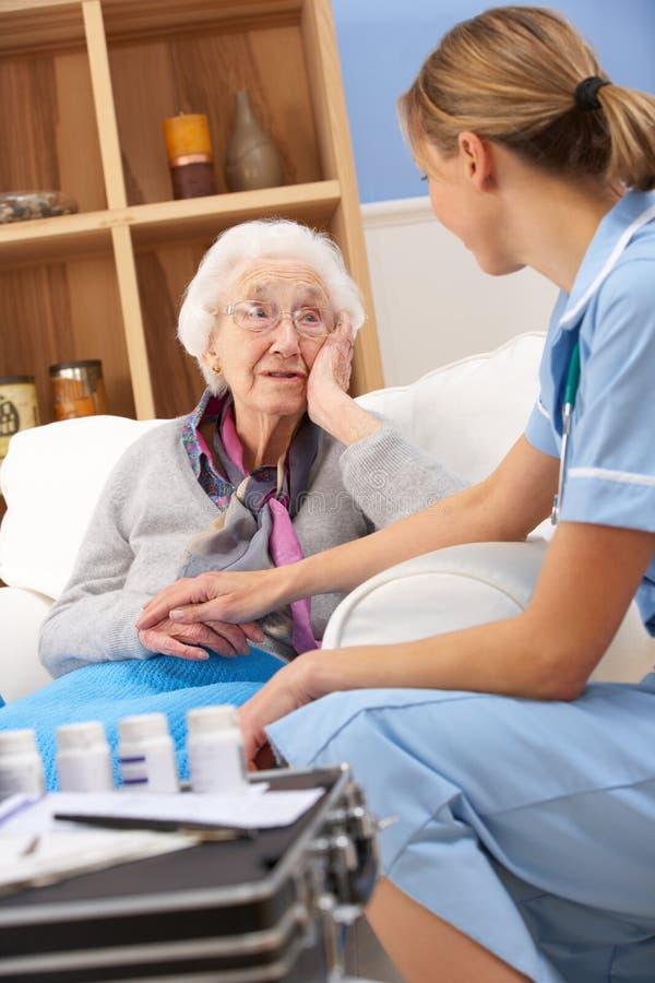 BRITISCHE Krankenschwester, die zu Hause ältere Frau besucht stockfotos
