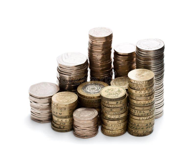 Britische Münzenstapel auf einem weißen Hintergrund stockbilder