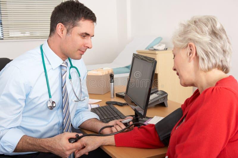 BRITISCHER Doktor, der Blutdruck der älteren Frau nimmt stockbild