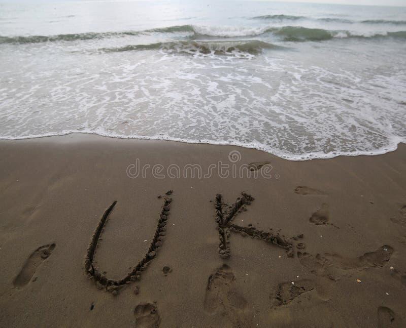 BRITISCHER Text geschrieben auf den Sand des Strandes nahe dem Meer lizenzfreie stockbilder
