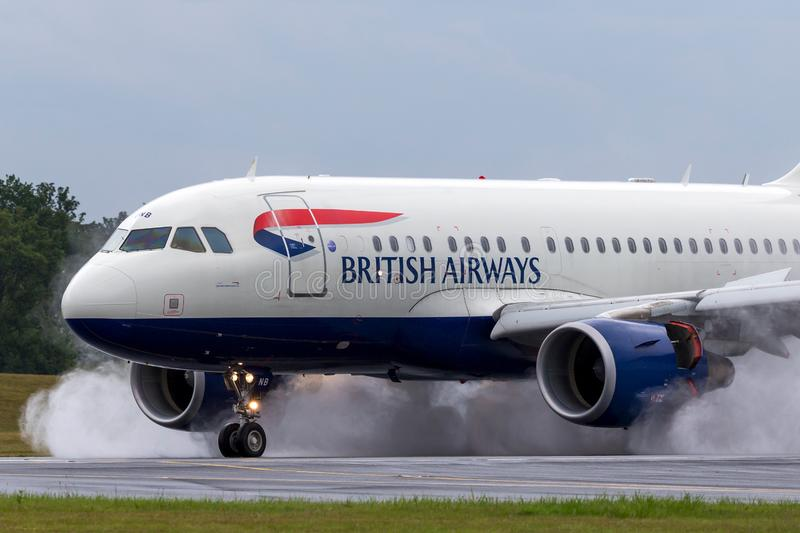 British Airways Airbus A318-112 aircraft G-EUNB landing on the wet runway with reverse thrust spraying water. Farnborough, UK - July 19, 2014: British Airways royalty free stock photography