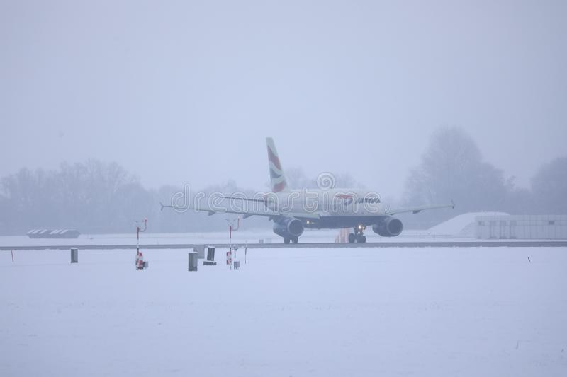 British Airways Airbus taxiing on snow, MUC Airport. British Airways jet doing taxi in Munich Airport, Munchen Flughafen. Winter with snow royalty free stock images