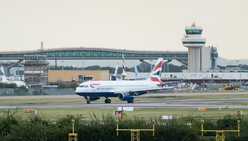 A British Airways Airbus A320-232 turns off the runway in front of the air traffic control tower after landing. London Gatwick Airport, UK- August 07 2019: A stock image