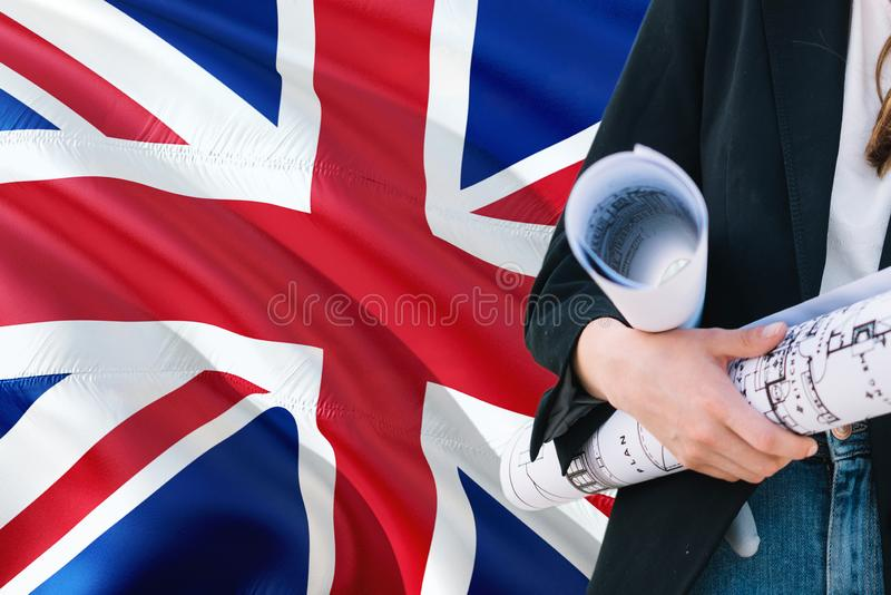 British Architect woman holding blueprint against United Kingdom waving flag background. Construction and architecture concept stock photography