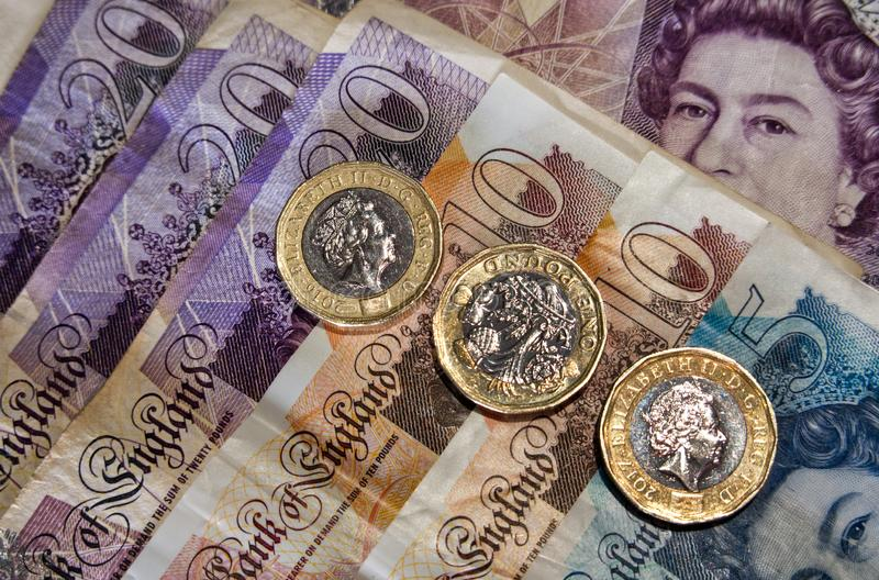 One pound coins and bank notes stock image