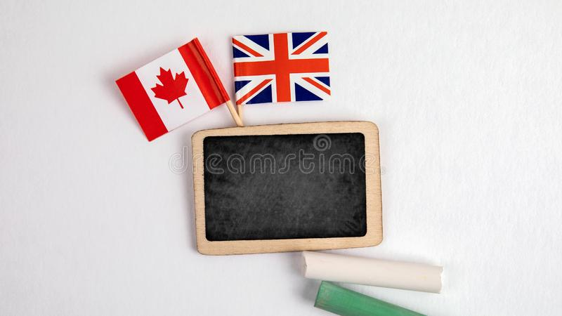 British and Canadian flags. Small whiteboard with chalk. Top view on a white background. Mockup, copy space royalty free stock photo
