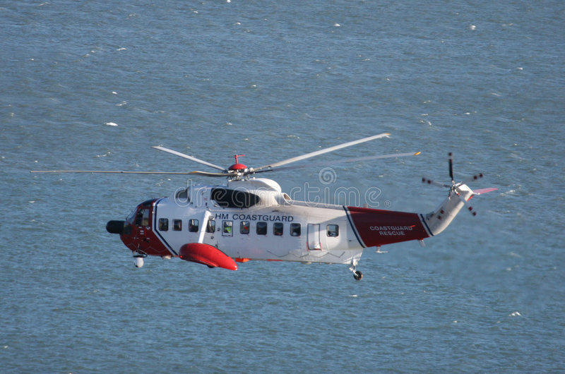 British Coastguard Chopper. Coastguard helicopter hovering above the sea, viewed from cliff-top perspective stock images