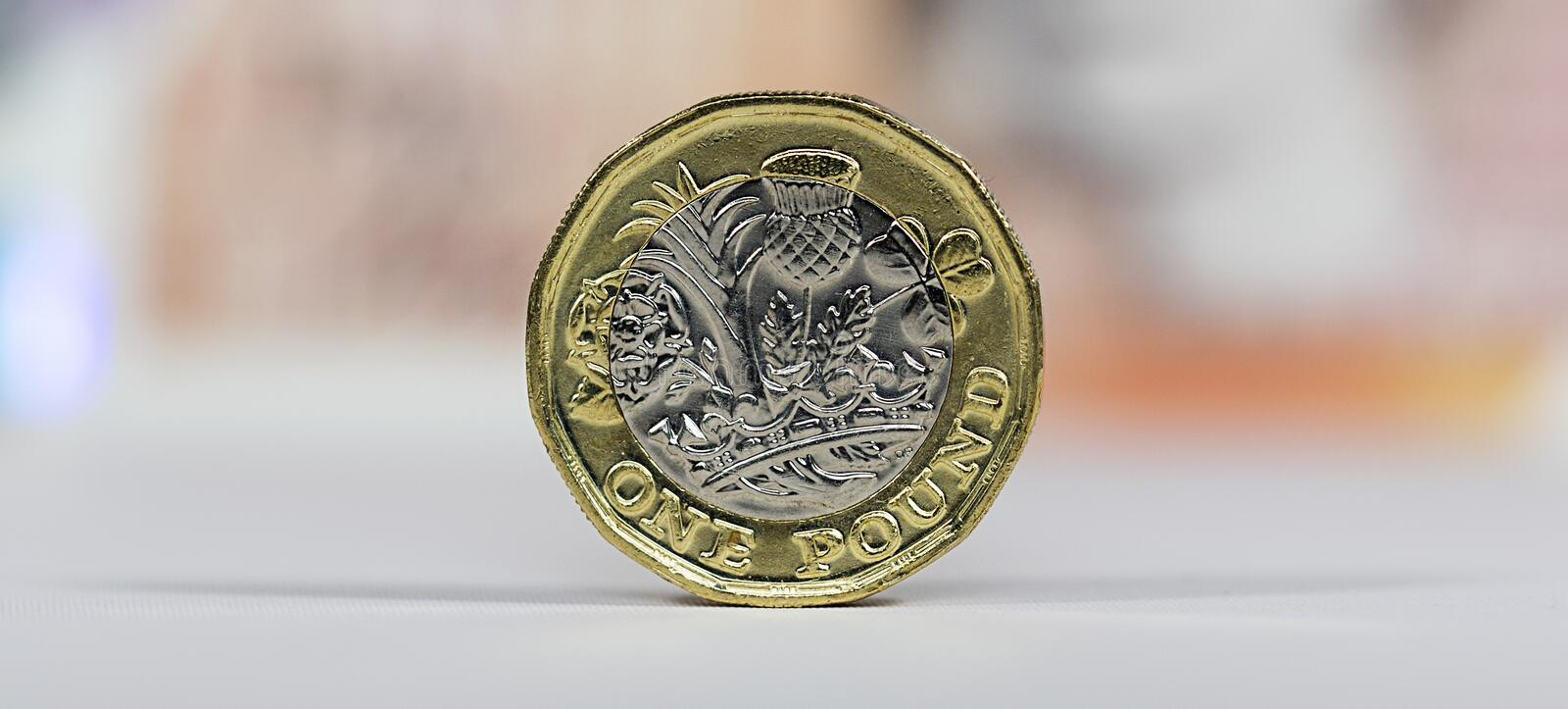 British Currency - New Polymer Ten Pound Note. London, UK: January 03, 2017: British one pound coin with a ten pound note background in a panoramic format. Both royalty free stock photos