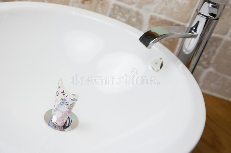 British Currency. Throwing money down the drain stock photo
