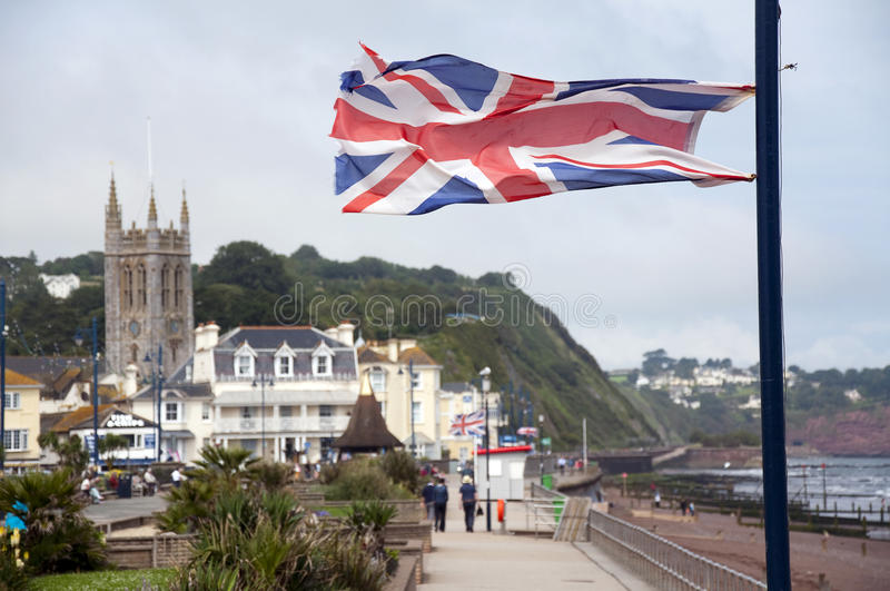 British flag at English seaside town. British flag in a strong wind on a promenade at small English seaside town, Teignmouth, Devon, England. UK royalty free stock photography