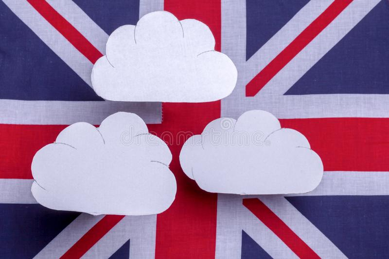British flag with three white clouds floating above. British union jack flag with three clouds floating over the flag. Red white and blue country symbol with royalty free stock image