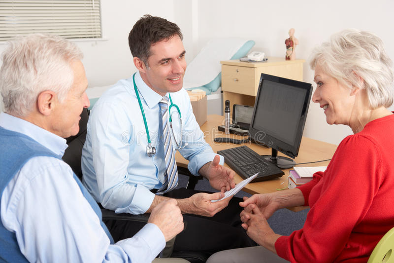 British GP talking to senior couple in surgery. Smiling stock photography