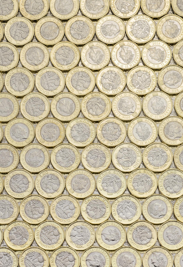 British money, new pound coins background laid flat. New pound coins background laid flat. Overhead point of view. The British bimetallic coin was introduced in stock photos