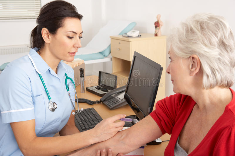 British nurse giving injection to senior woman stock photos