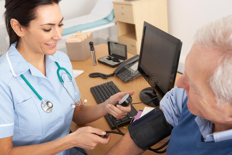 British nurse taking senior man's blood pressure. In nurse's office royalty free stock photography