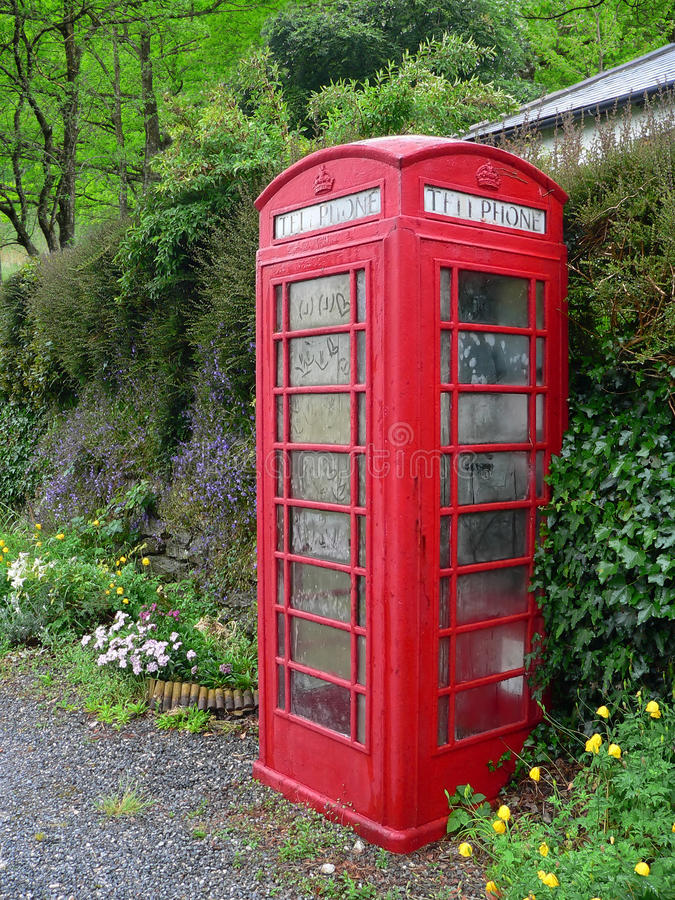 British phonebox in the greenery. Old fashioned dusty and weathered british phone box, beside a wall in the greenery royalty free stock photos