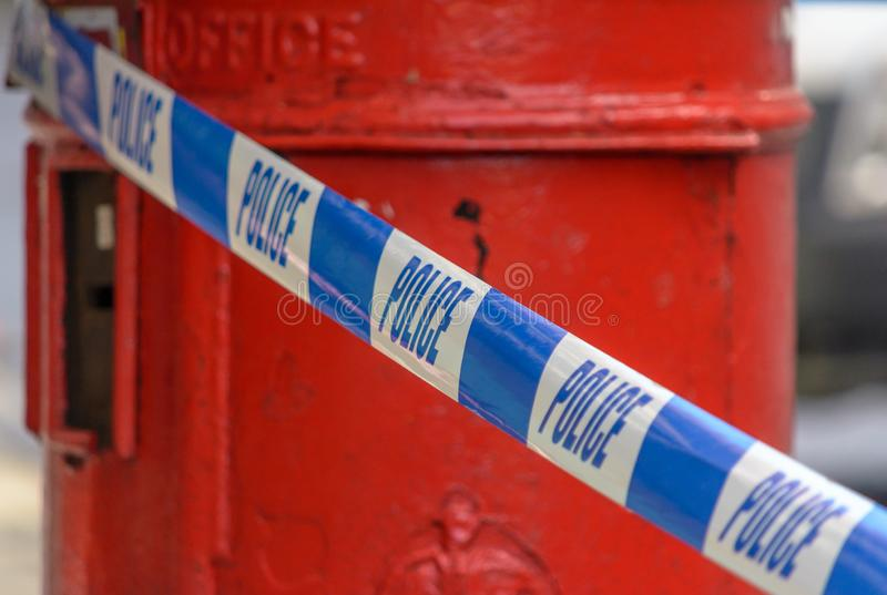 British Police Tape In Front Of Red Post Box royalty free stock photo