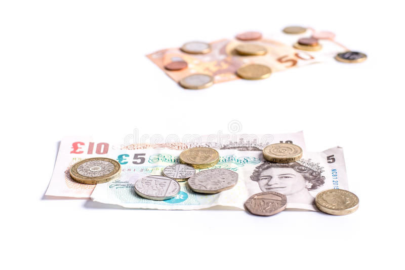 British Pound notes and coins and Euro notes and coins on white stock photography