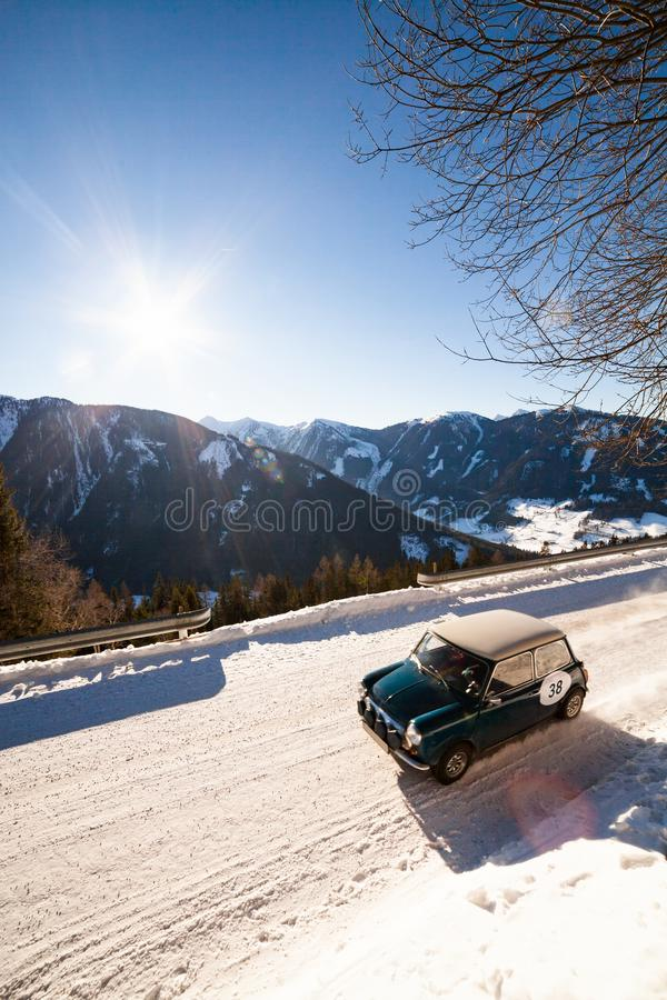 Vintage racing car driving classic rally on snow covert road. British racing green vintage car driving a classic rally on snow covert road on mountain Planai in royalty free stock photography