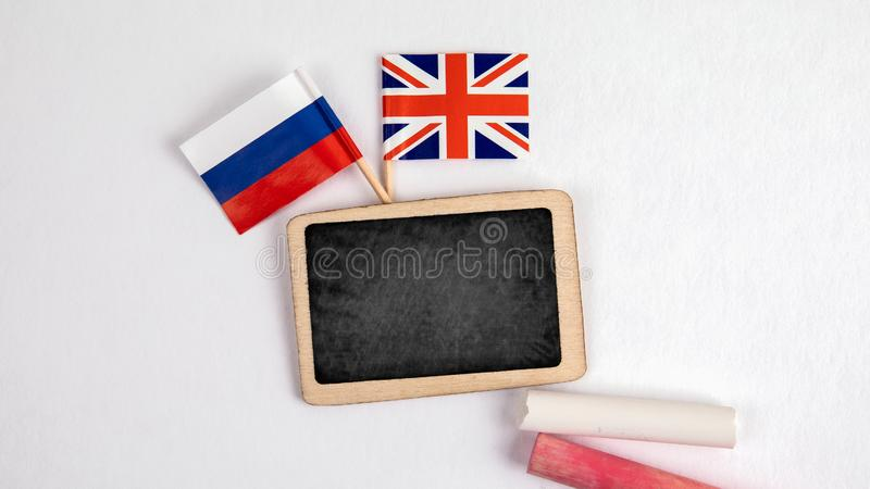 British and Russian flags. Small whiteboard with chalk. Top view on a white background. Mockup, copy space stock photography