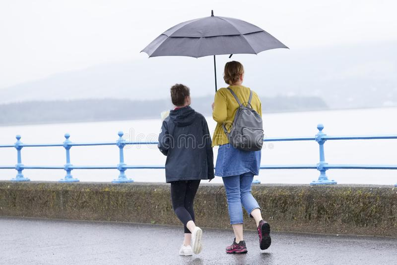 British wet summer umbrella weather with mother and daughter. Uk royalty free stock images