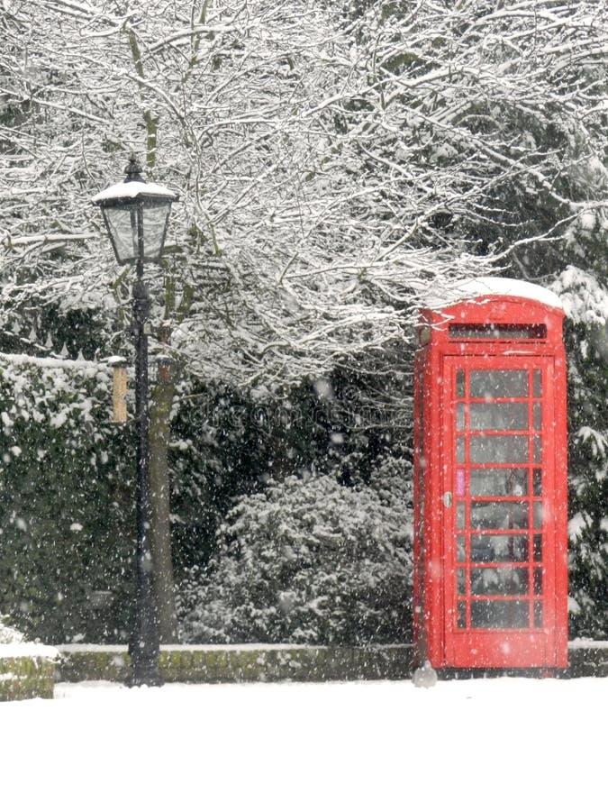 Brittisk röd telefonask i snön arkivfoto