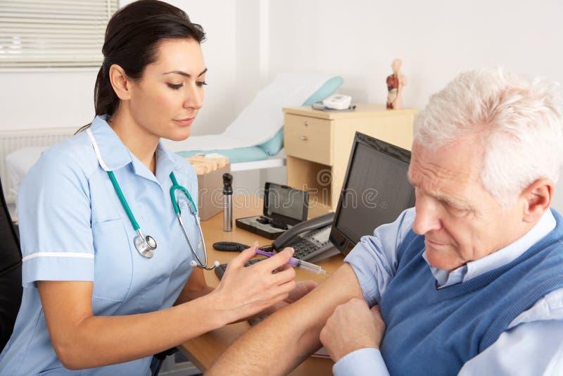 Brittisk sjuksköterska som ger injektionen till den höga manen arkivbilder