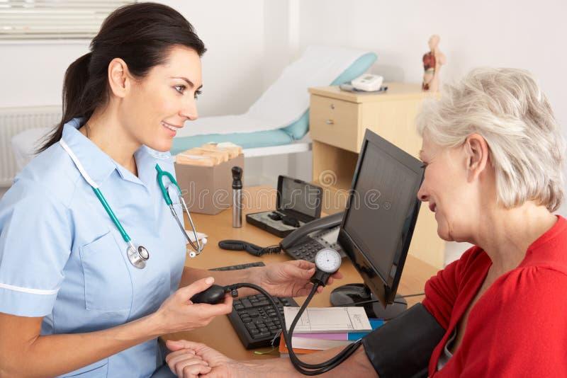 Brittisk sjuksköterska som tar kvinna blodtryck royaltyfri foto