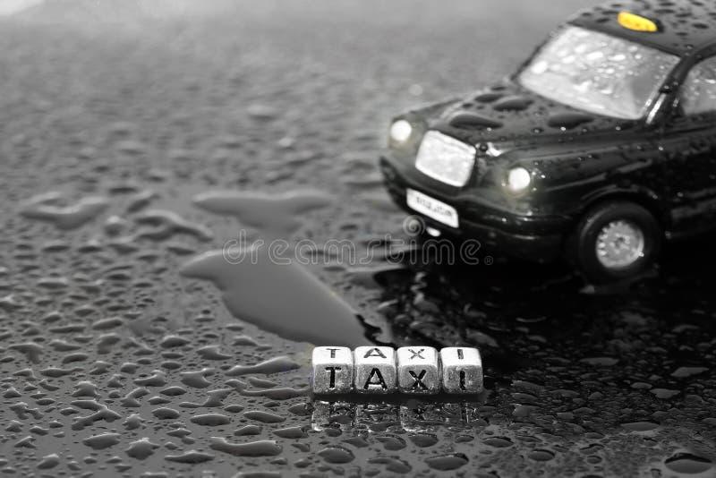 Brittisk traditionell svart bil för taxitaxileksak med ordtaxien på pärlor arkivbilder