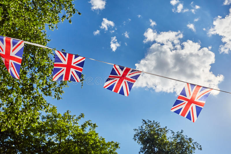 Brittisk Union Jack bunting sjunker mot himmel- och gräsplanträd arkivfoto