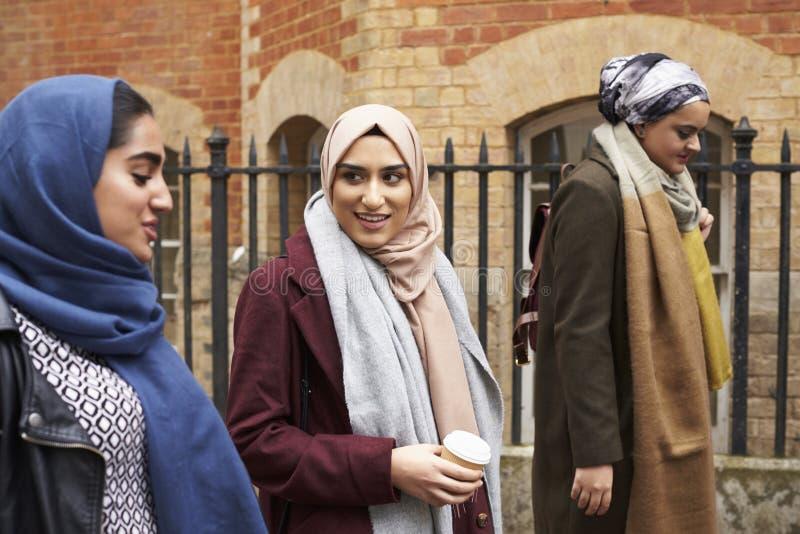 Brittiska muslimska kvinnliga vänner som går i stads- miljö royaltyfri fotografi