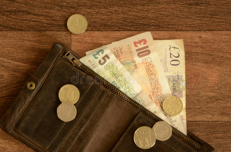 Brittiska pengar i brun läderplånbok arkivbild