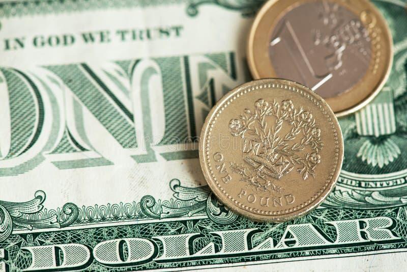 Brittiskt pund- och euromynt med US dollarsedlar royaltyfri foto
