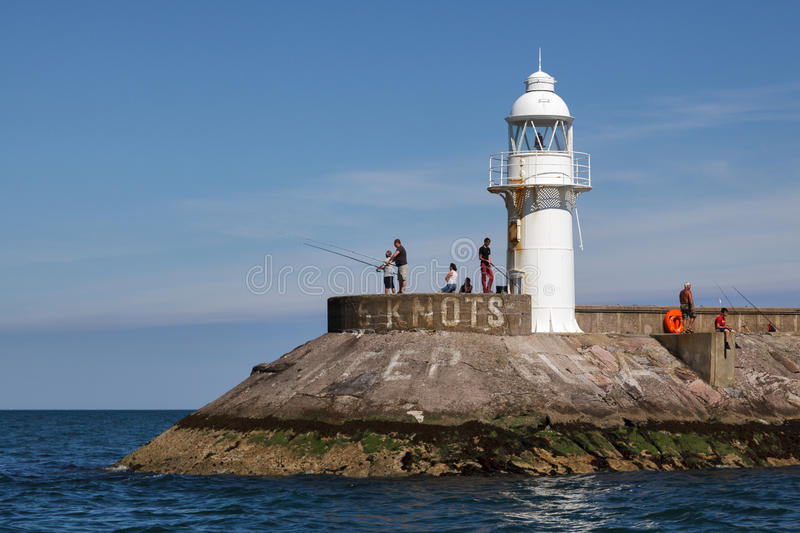 BRIXHAM, DEVON/UK - JULY 28 : People fishing near the lighthouse. At Brixham harbour in Devon on July 28, 2012. Unidentified people royalty free stock image