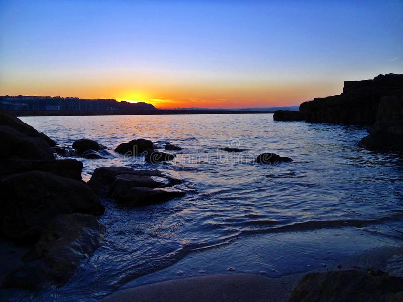Brixham solnedgång över den Shoalstone stranden royaltyfri foto