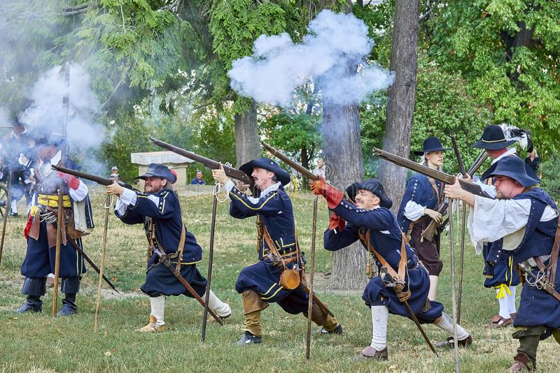 Historical reenactment Day of Brno. Actors in historical Infantry costumes shoot a musket, gunpowder smoke is around them. Brno, Czech Republic - August 18, 2018 royalty free stock photos