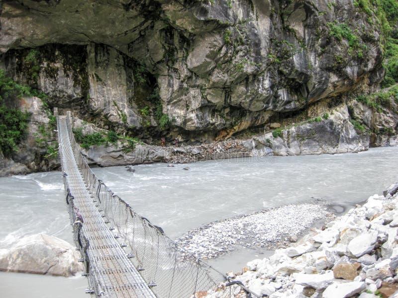 Bro över den Marsyangdi floden nära den Tal byn - Nepal royaltyfri bild