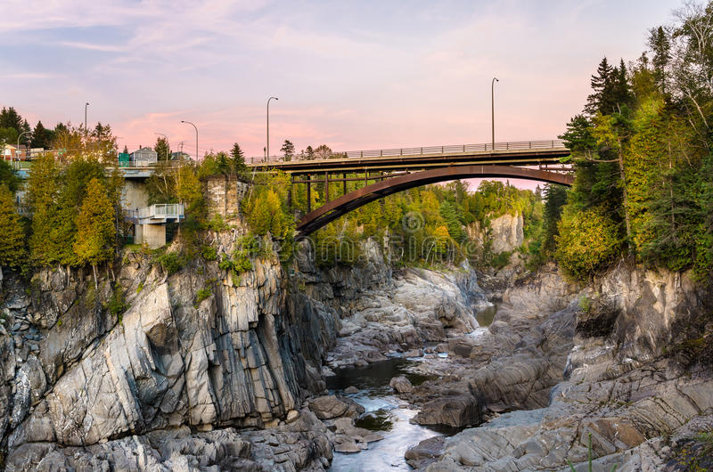 Bro över en djup klyfta på solnedgången arkivbild