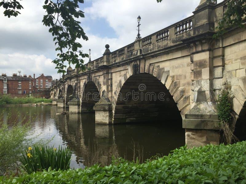 Bro över lugna vatten med reflexioner royaltyfria bilder